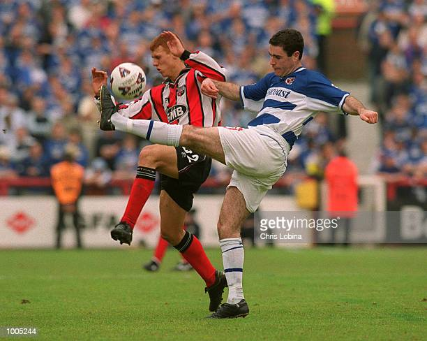 Andy Hughes of Reading clears the ball from Steve Sidwell of Brentford during the Nationwide Division Two match between Brentford and Reading at...