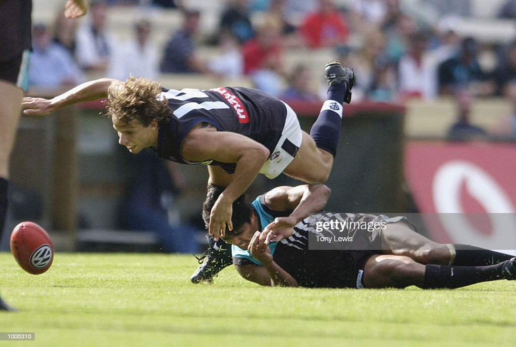 David Gallagher #14 for Carlton tumbles over Che Cockatoo-Collins #12 for Port in the match between Port Power and the Carlton Blues in round 4 of the AFL played at Football Park in Adelaide, Australia. Port Adelaide 23.10 (148) defeatedCarlton 14.11 (95) DIGITAL IMAGE Mandatory Credit: Tony Lewis/Getty Images