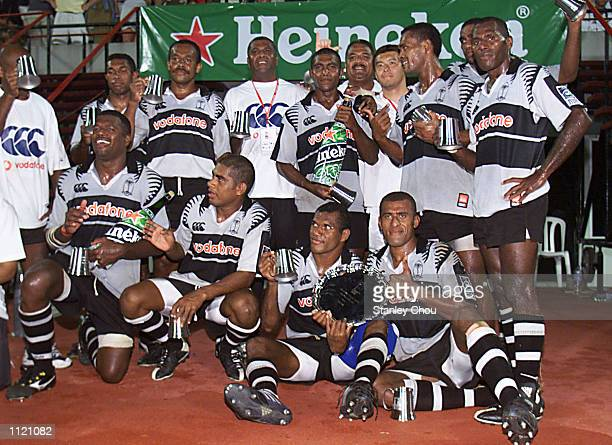 Fiji Players pose for photographs after they won the plate during the Singapore Sevens plate final between Fiji and Samoa during the IRB World Rugby...