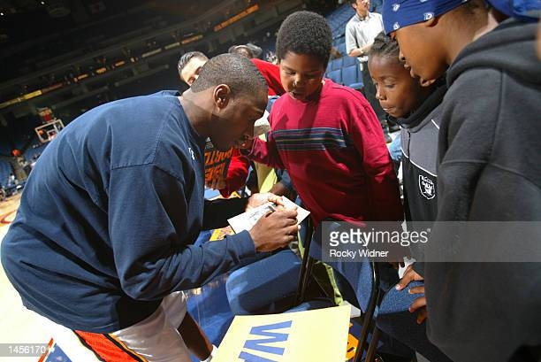 Gilbert Arenas of the Golden State Warriors signs autographs for some fans before the game against the Portland Trail Blazers at The Arena in Oakland...