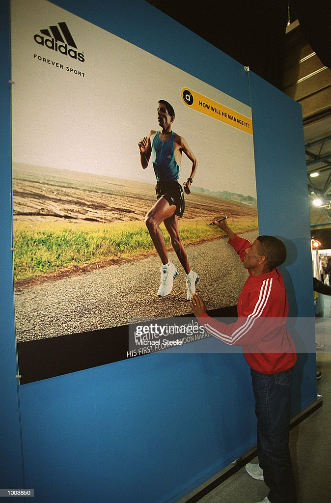 Marathon debutant Haile Gebrselassie (left) of Ethiopia signs a poster of himself at the adidas stand at the London Marathon Exhibition at the London Arena in Docklands, London. Mandatory Credit: Michael Steele/Getty Images