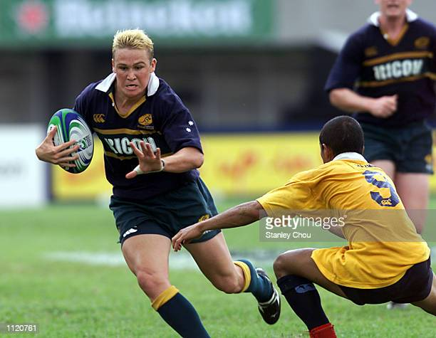 Matthew Giteau of Australia is checked by Nor Hazmin Ghamili of Malaysia during the Singapore Sevens between Australia and Malaysia during the IRB...