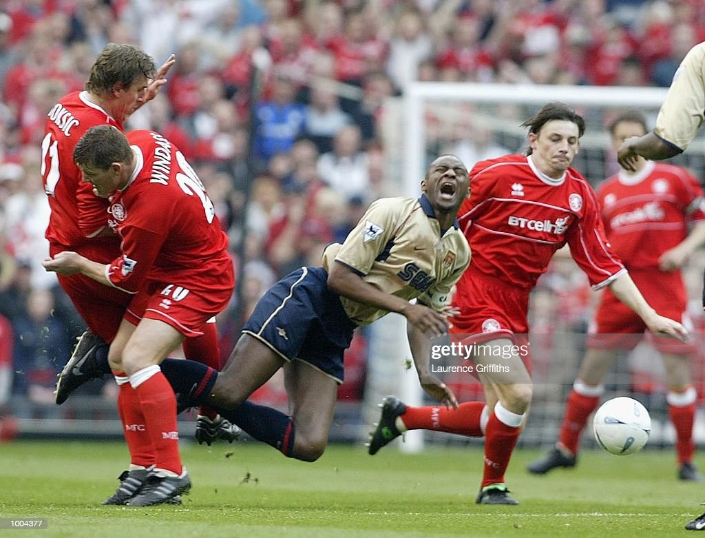 Patrick Vieira of Arsenal goes down from the challenge by AIen Boksic of Boro during the AXA sponsored FA Cup semi final tie between Middlesbrough v Arsenal at Old Trafford Stadium, Manchester. DIGITAL IMAGE. Mandatory Credit: Laurence Griffiths/Getty Images