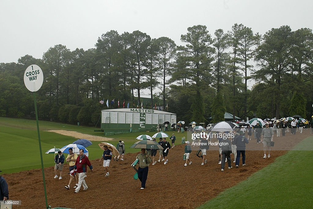 Patrons cross the first fairway in the rain during the third day of the Masters Tournament from the Augusta National Golf Club in Augusta, Georgia. DIGITAL IMAGE. EDITORIAL USE ONLY Mandatory Credit: Andrew Redington/Getty Images