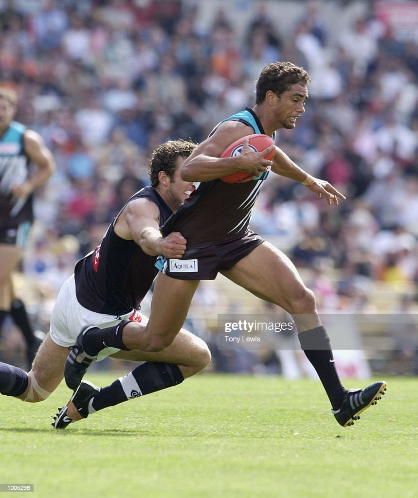 Peter Burgoyne #7 for Port is tackled by Simon Beaumont #29 for Carlton in the match between Port Power and the Carlton Blues in round 4 of the AFL played at Football Park in Adelaide, Australia. DIGITAL IMAGE Mandatory Credit: Tony Lewis/Getty Images