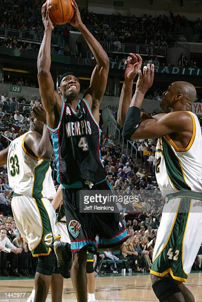 Stromile Swift of the Memphis Grizzlies goes between Jerome James and Vin Baker of the Seattle SuperSonics for a bucket at Key Arena in Seattle...