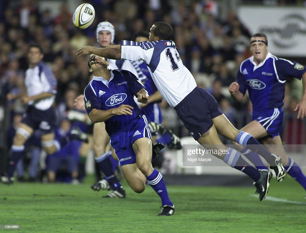 Wylie Human #14 of the Bulls flies throught the air to tackle Carlos Spencer #10 during the Super 12 game between the Blues and the Bulls at Eden Park Auckland, New Zealand. DIGITAL IMAGE. Mandatory Credit: Nigel Marple/Getty Images