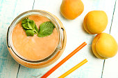 Apricot smoothies in a glass jar and apricots on a wooden background.