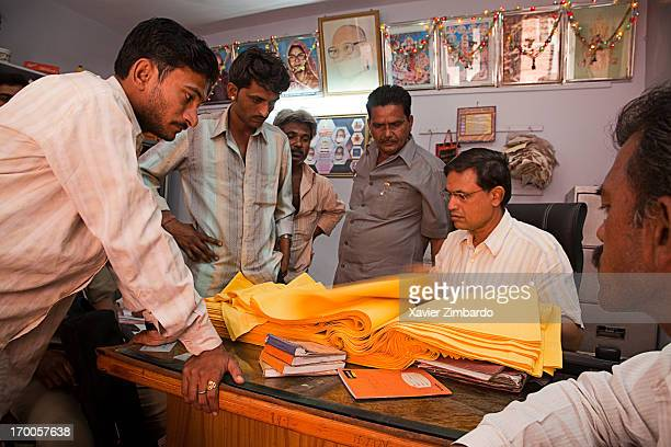 Officers and workers check quality of dyeing on April 01 2009 at an office of a fabric dyeing factory in Rajasthan India The pieces of dyed cloth lie...