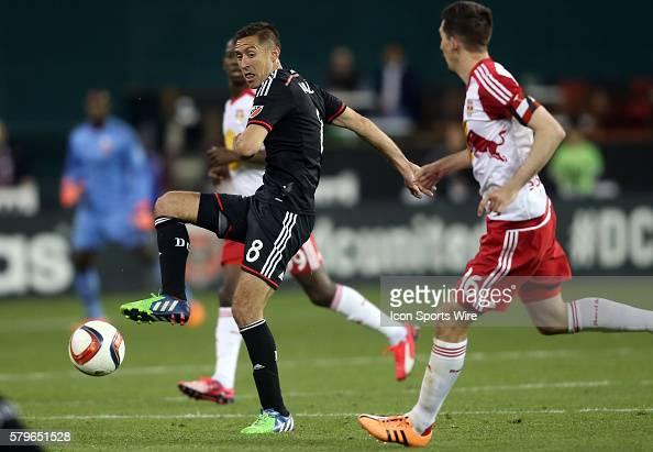 DC United midfielder Davy Arnaud slips a pass away from New York Red Bulls midfielder Sacha Kljestan during a MLS match at RFK Stadium in Washington...