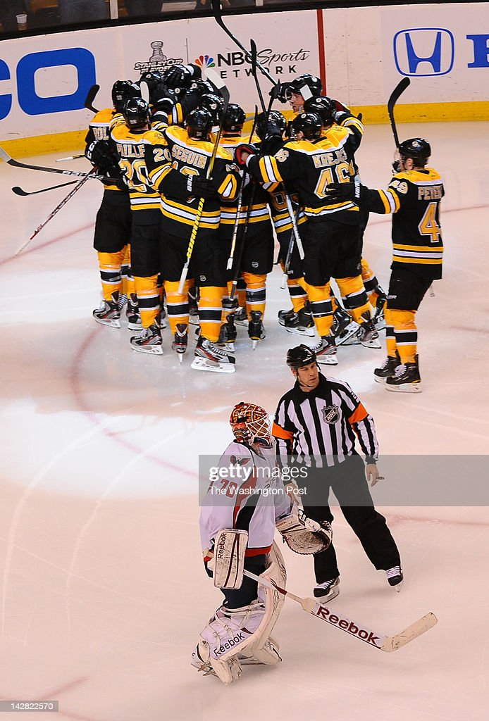 BOSTON, MA April 12, 2012 Washington Capitals goalie Braden Holtby (70) skates off the ice as the Boston Bruins celebrate their 1-0 overtime win on a goal by Bruins center Chris Kelly (23)on April 12, 2012 in Boston, MA