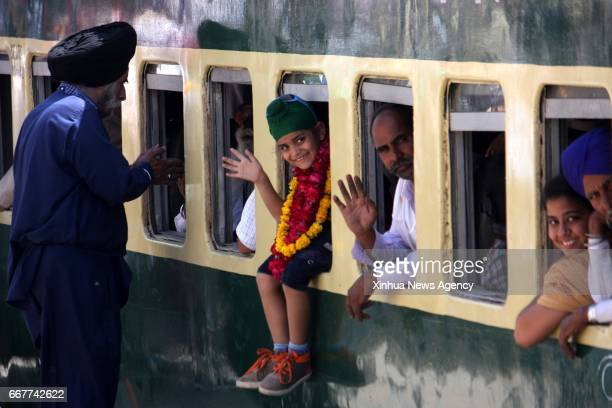 LAHORE April 12 2017 Indian Sikh pilgrims wave from a train as they arrive at Wagah Railway Station in eastern Pakistan's Lahore on April 12 to...