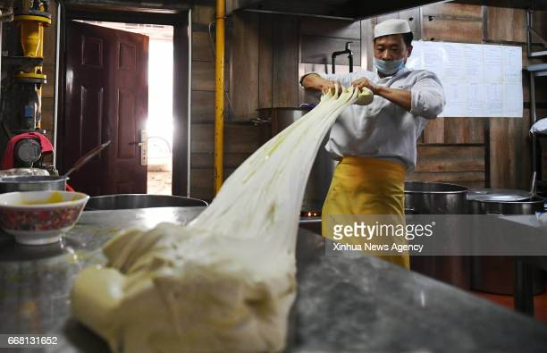 LANZHOU April 13 2017 A chef mixes dough to make beef noodle at a noodle restaurant in Lanzhou capital of northwest China's Gansu Province April 12...