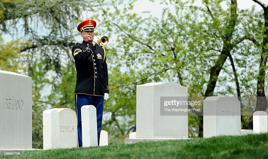 A bugler plays taps during the burial service for U.S. Army Lt. Col. Don Carlos Faith Jr., a Medal of Honor recipient killed in Korean War , on April 17 2013 in Arlington, VA