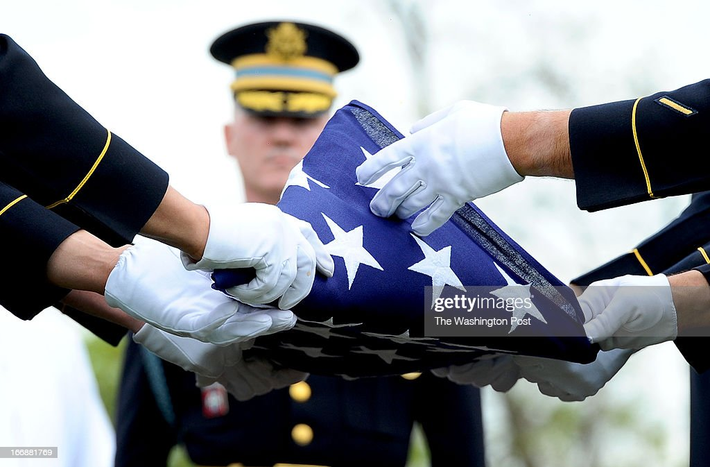 Members of the U.S. Army's 3rd Infantry Regiment 'The Old Guard' fold the flag during the burial service for U.S. Army Lt. Col. Don Carlos Faith Jr., a Medal of Honor recipient killed in the Korean War 1950. The service was held at Arlington National Cemetery on April 17 2013 in Arlington, VA