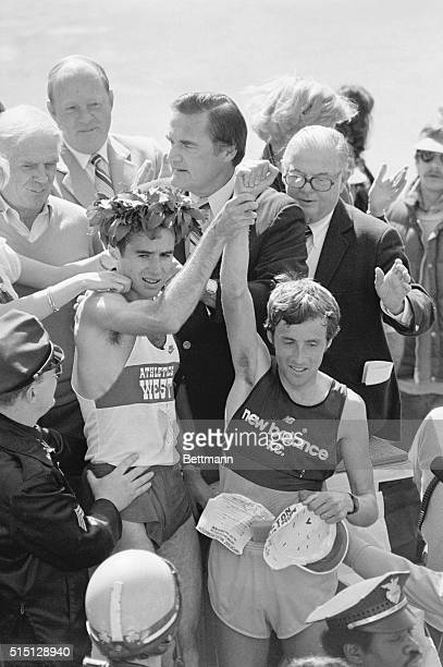 April 19 1982 Boston Alberto Salazar of Wayland MA wearing the victor's laurel wreath holds up arm of second place finisher Dick Beardsley of Rush...