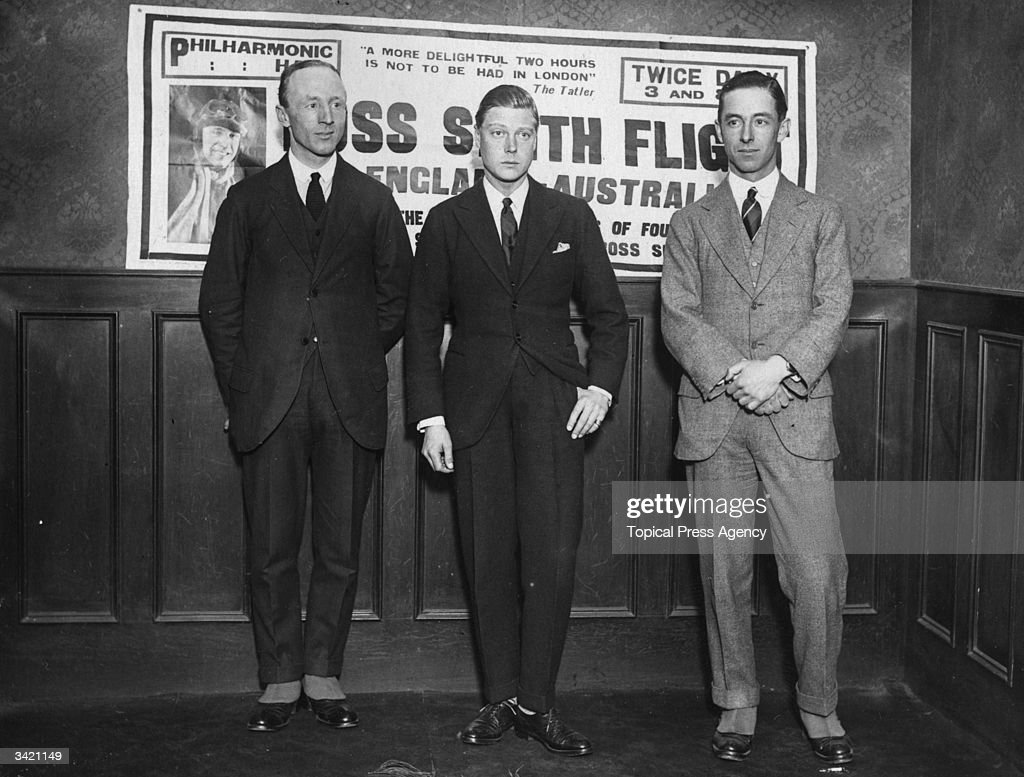 Aviator brothers Sir Ross Smith (1892 - 1922), left, and Sir Keith Smith (1890 - 1955) with Edward, Prince of Wales (1894 - 1972) in the centre. They are standing in front of a poster advertising a series of talks by Ross Smith.