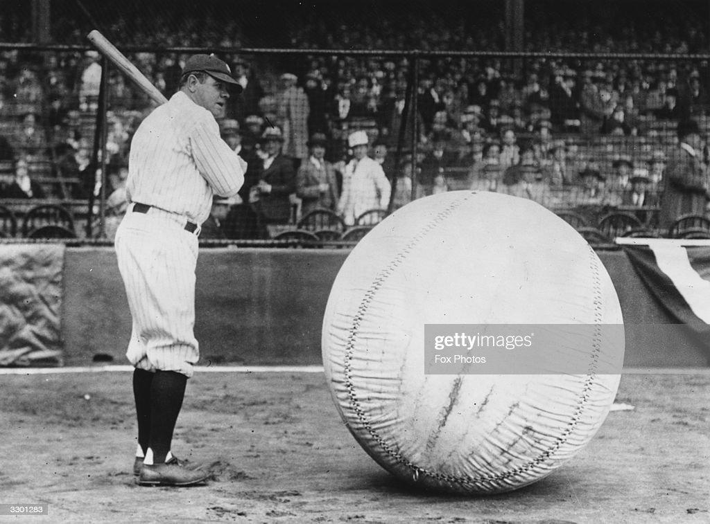 Baseball player Babe Ruth taking a swipe at an enormous ball