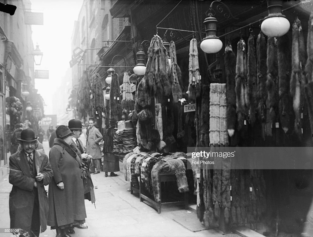 Fur coats and accessories hang outside a fur stall in Berwick Street Market, London.