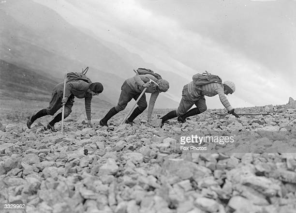 Three women mountaineers scramble across a rock strewn area of Ben Nevis Ben Nevis in the Grampian Mountains near Fort William is the tallest point...