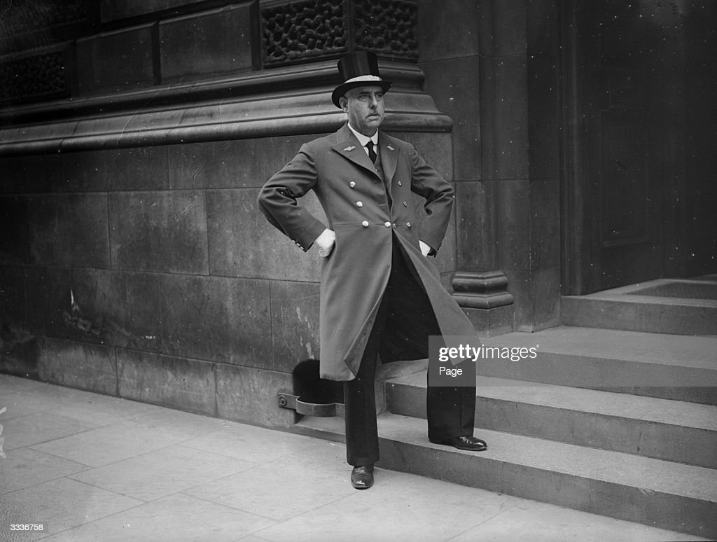Mr G Morgan, hall porter at the Air Ministry in London, looks out accusingly from the steps of his building.