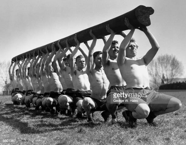 Men from the AntiAircraft Divisional School of Physical Training carrying a telegraph pole during training for ravine and river crossing
