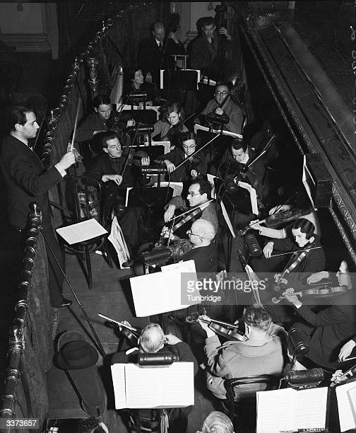 Walter Susskind conducts an orchestra during a production of Offenbach's operaballet 'Tales of Hoffmann' at the Strand Theatre London