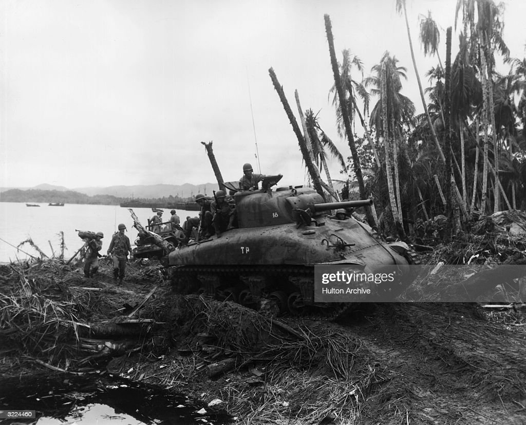 A US Sherman medium tank carrying marksmen rolls inland from Humboldt Bay clearing a path through the jungle for the infantry after a threeweek500ton...