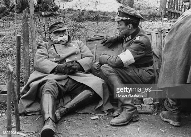 A German Army Medical Officer comforts a Nazi Chief of Police who was injured in his efforts to escape from the advancing US 7th Army troops