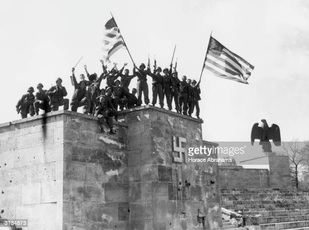 Men of the 45th division of the US 7th Army wave American flags from the dais of the Luitpold Arena in Nuremberg after capturing the city It was in...