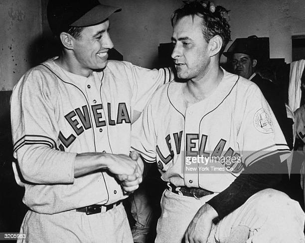 Cleveland Indians pitcher Bob Feller shakes hands in a locker room with his teammate Frank Hayes congratulating him for hitting a gamewinning home run