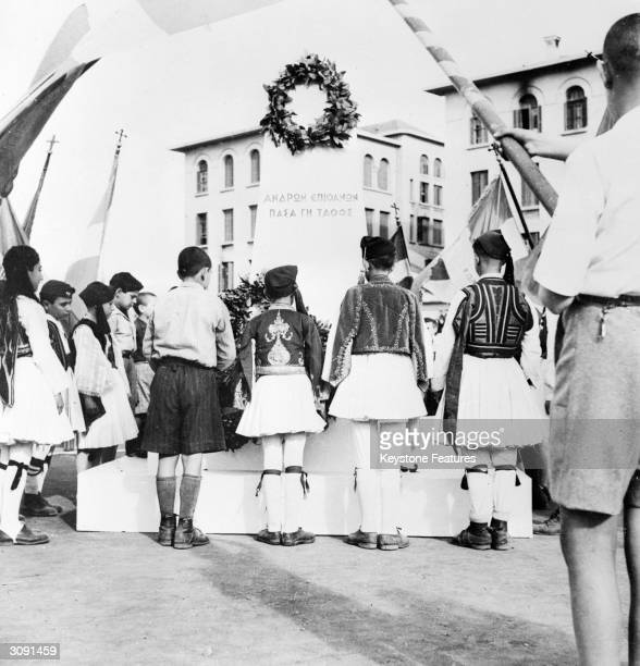 Greek schoolchildren in national costume place wreaths on a monument in Salonika erected to the memory of the heroes of the 1821 uprising or Greek...
