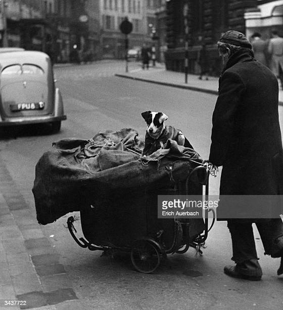 In a street in Leeds Yorkshire an old man in ragged clothing pushes a pram containing all his wordly possessions his small dog takes a ride as well...