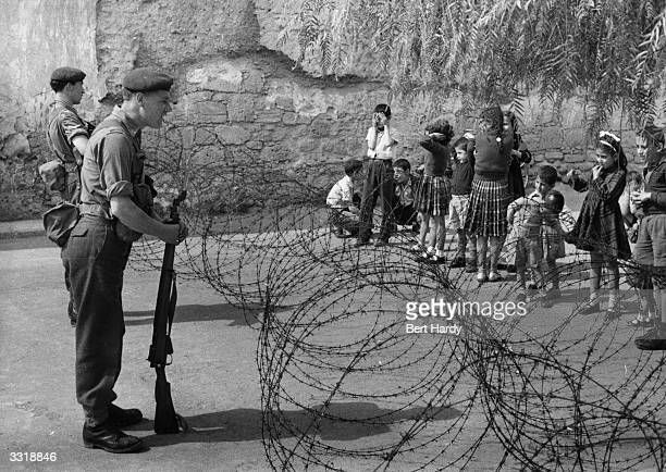 British soldiers in a mountain village in Cyprus erect barbed wire barricades in their hunt for EOKA terrorists The village children are fascinated...