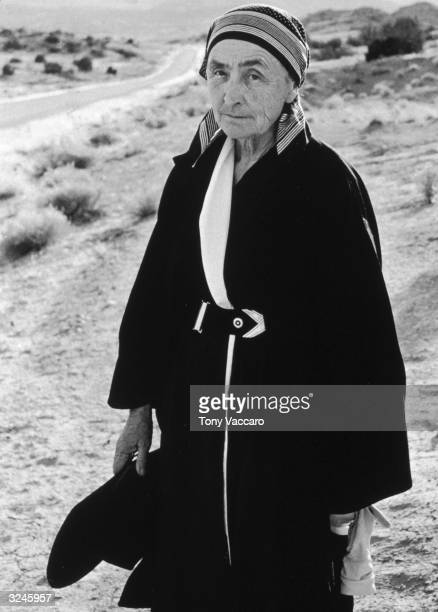 American painter Georgia O'Keeffe stands in the sand on the side of a road wearing a long black coat and a bandana New Mexico