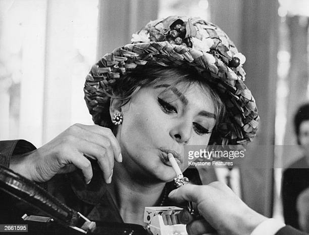 Italian actress Sophia Loren accepting a light at the Turin flower show