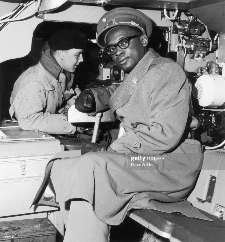 General Joseph Mobutu (later Sese Seko Mobutu), Chief Commander of the National Congolese Army, examines the interior of an armored car during a tour of a military infantry school in England.