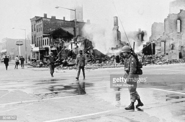 A Black man crosses a street past soldiers and a bombed building during the race riots that followed Martin Luther King's assassination Washington DC
