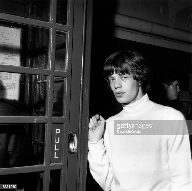 Rolling Stones vocalist Mick Jagger leaning on a telephone box