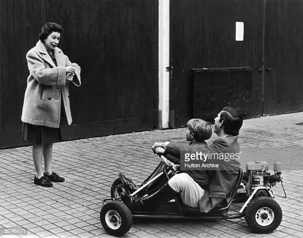 Charles Prince of Wales riding a gokart with his younger brother Prince Edward whilst Queen Elizabeth II looks on