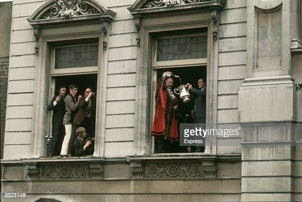 Photographers jostle for space in a window at Chelsea Town Hall London as Chelsea's mayor pours champagne into the FA Cup trophy held up by...