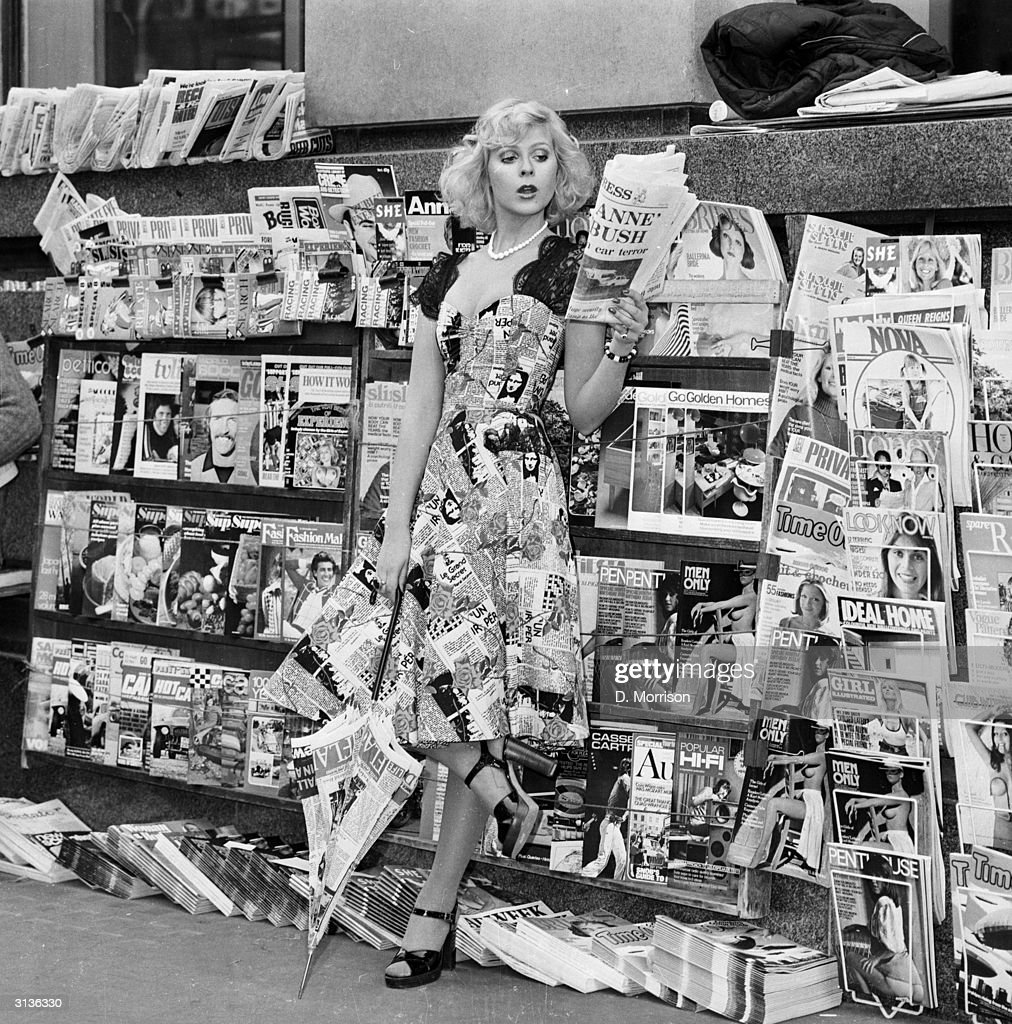 A model wearing a dress with a newspaper print design