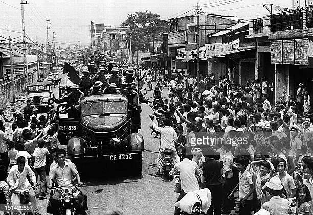 April 1975 photo shows Saigon residents taking to the street to welcome the arrival of communist troops on trucks 30 April 1975 after the fall of...