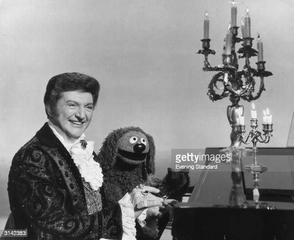 Flamboyant American pianist singer and entertainer Liberace playing the piano with a little help from the Muppets piano dog Rowlf