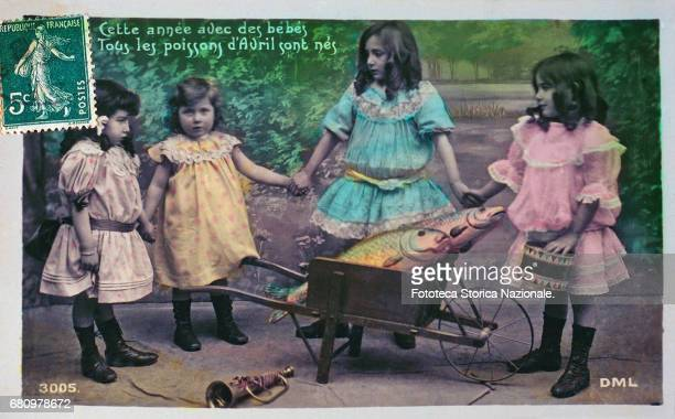 children around to a wheelbarrow that carries two great fish of April The phrase up recites 'Cette annèe avec des bébés Tous les poissons of Avril...