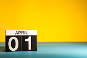 April 1st. Day 1 of april month, calendar on table with yellow background. Spring time, empty space for text.
