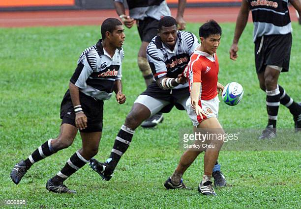 Gary Tan Ley Keong of Singapore is held by Ilaitia Takaladau of Fiji during the Malaysian Sevens first round match between Singapore and Fiji during...