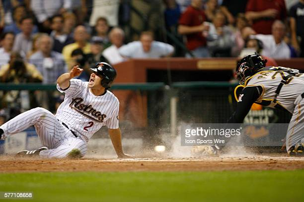 Houston Astros center fielder Chris Burke left looks for the call to see if Pittsburgh Pirates catcher Ronny Paulino got him out at home plate in the...