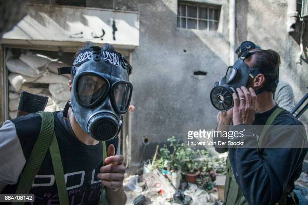 Rebel fighters of Liwa Tarhir al Sham wear gas masks after a suspected chemical weapon attack by Syrian government forces in Jobar a suburb of...