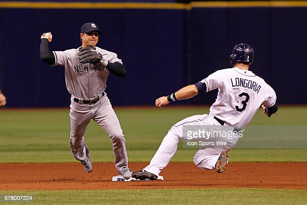 New York Yankees second baseman Brian Roberts makes the throw to first to turn a double play as Tampa Bay Rays third baseman Evan Longoria slides...
